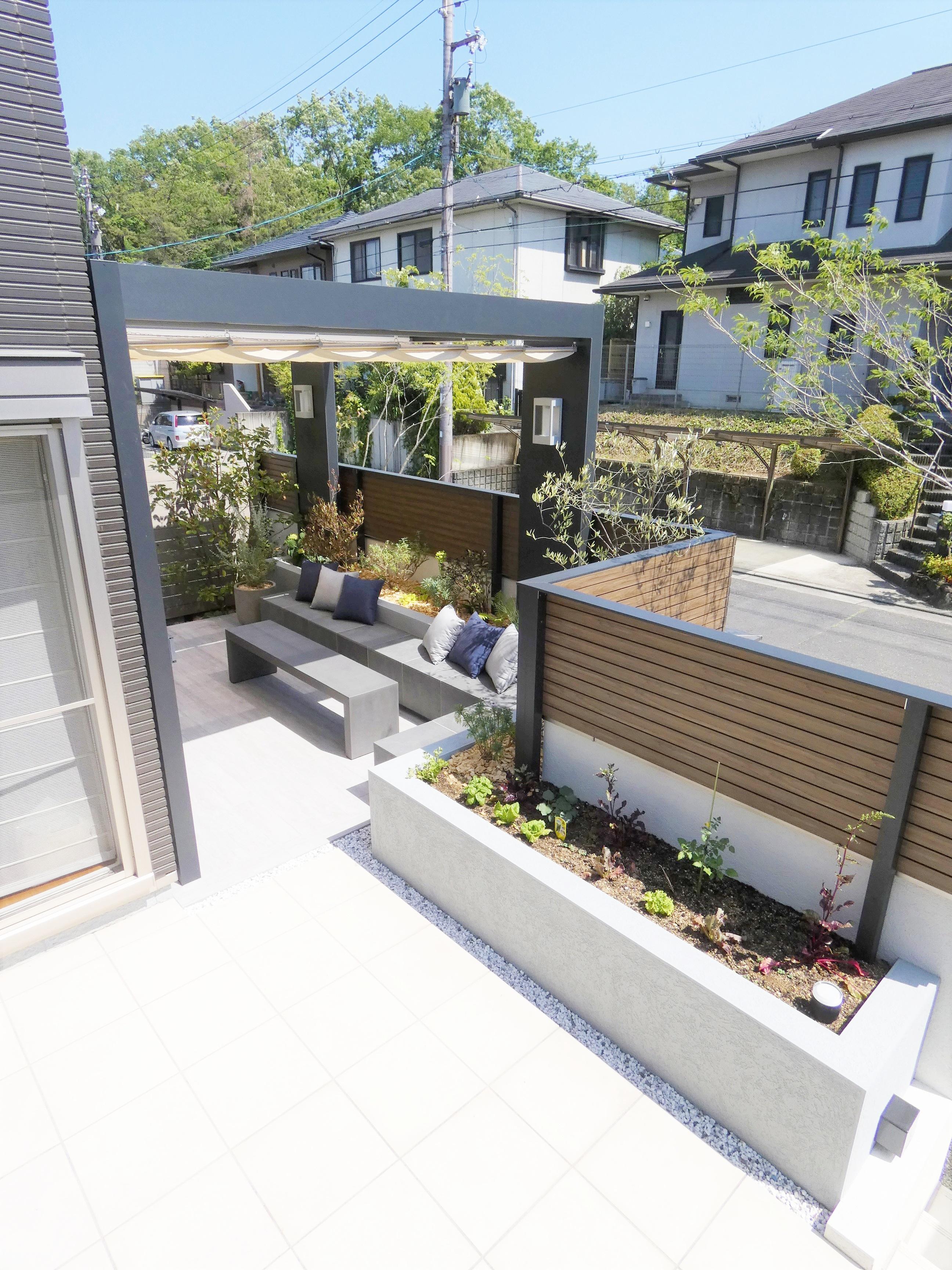白いテラスの奥にパーゴラ付きのベンチある庭をやや上から見たショット