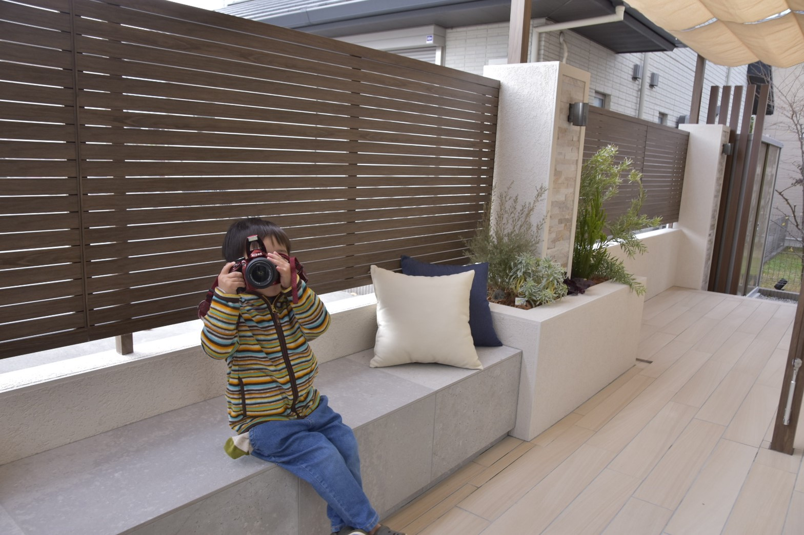 テラスのベンチでカメラを向ける子
